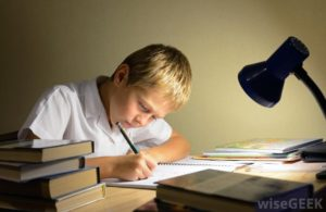 child-writing-with-books-and-desk-lamp